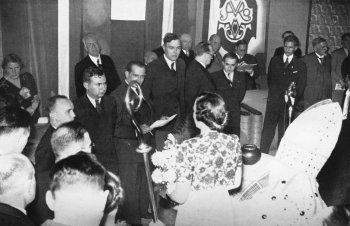 Przy mikrofonie ustawieni stoją (twarzami do fotografa) uczestnicyturnieju: (od lewej do prawej) Reshevsky, Fine, organizator, Euwe, Alechin, Flohr i Keres.